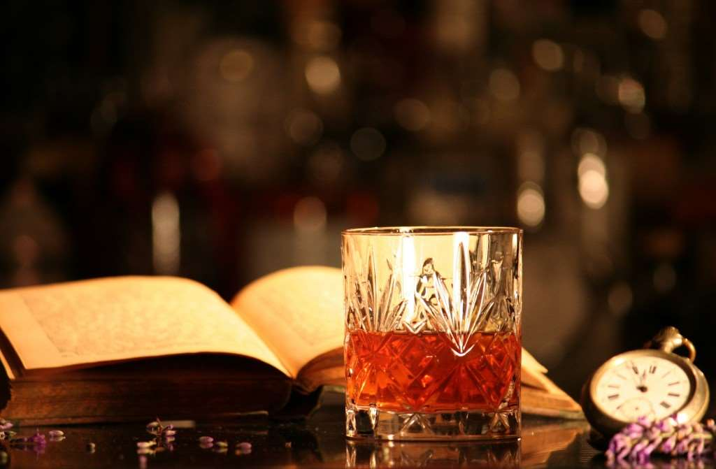 A colour picture of a glass of whiskey, a book and a pocket watch.