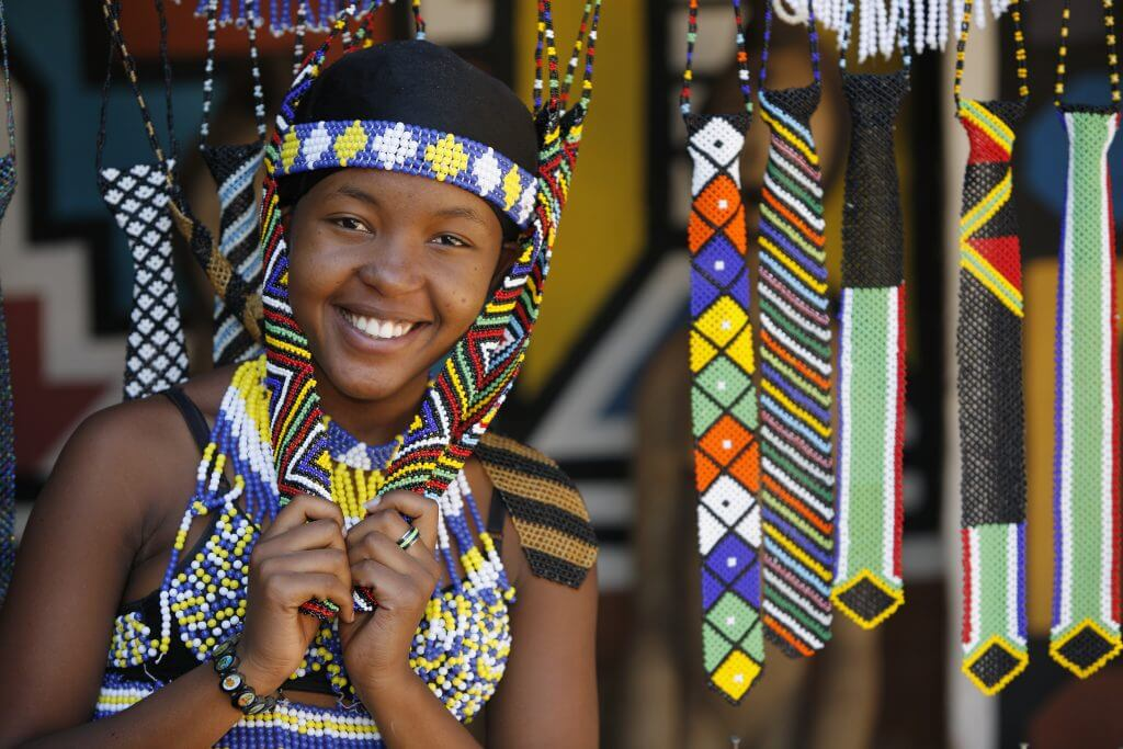"""A pretty young Zulu girl poses amongst beaded souvenirs that she has hand made and selling to visitors to this area of Kwazulu-Natal, in South Africa."""