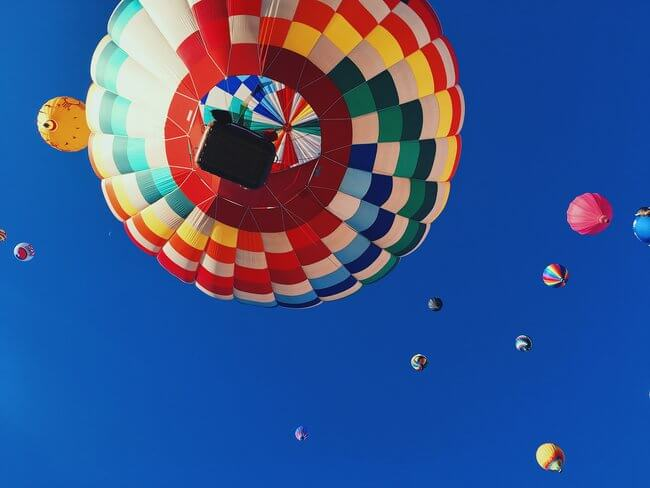 colourful hot air balloons flying above blue skies