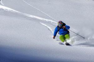 man skiing close up down slopes