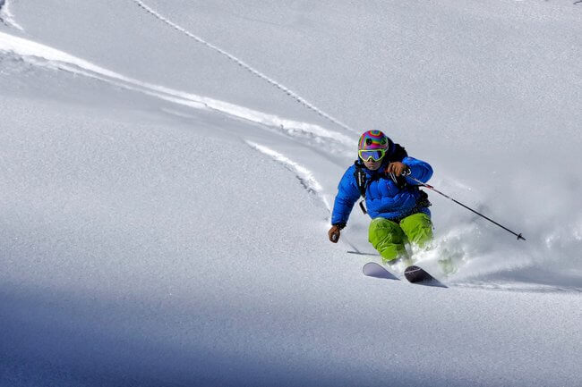 man skiing close up down slopes