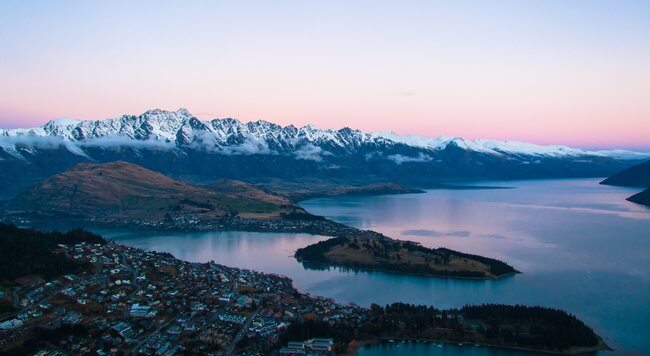 Queenstown view across lake and mountains pink sky