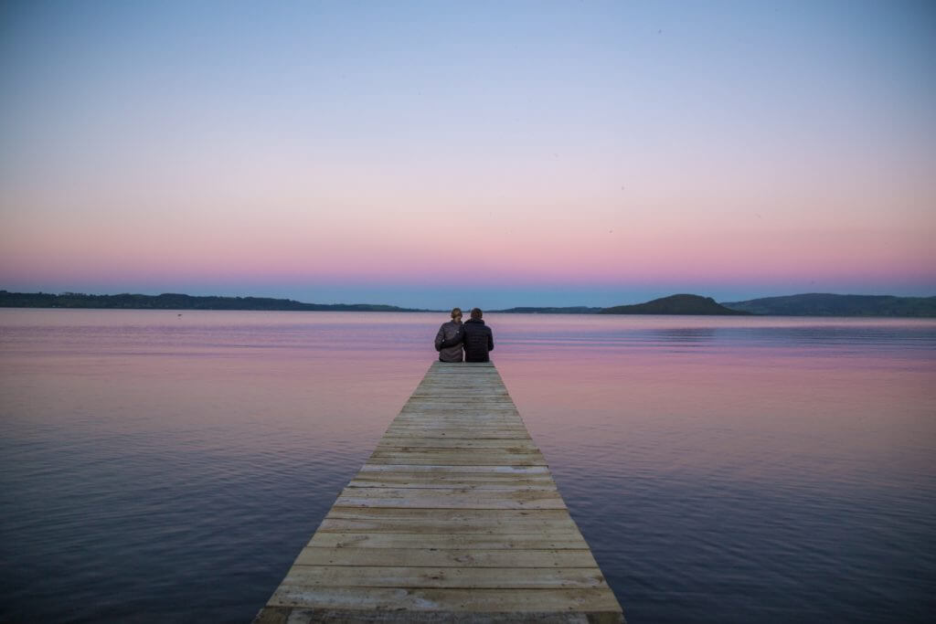 couple on dock at sunset lake rotorua new zealand