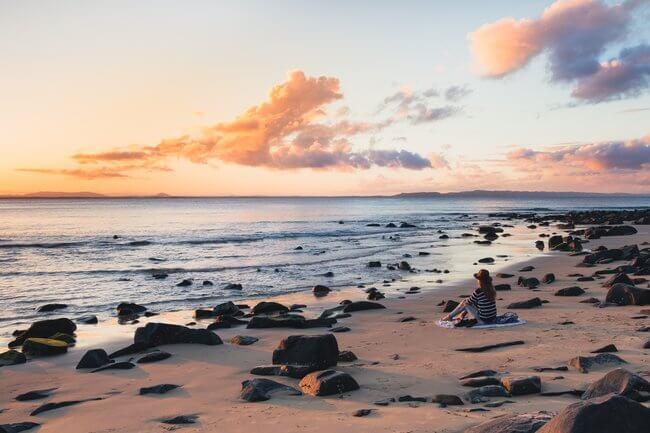 woman sitting on Noosa Beach at sunset Australia