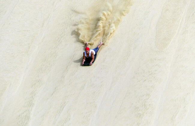 sand surfing down Te Paki Sand Dune New Zealand