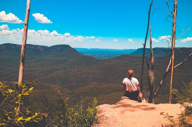 girl on rock edge over blue mountains Australia