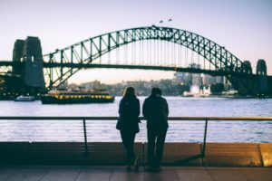 woman and man facing sydney harbour bridge dusk