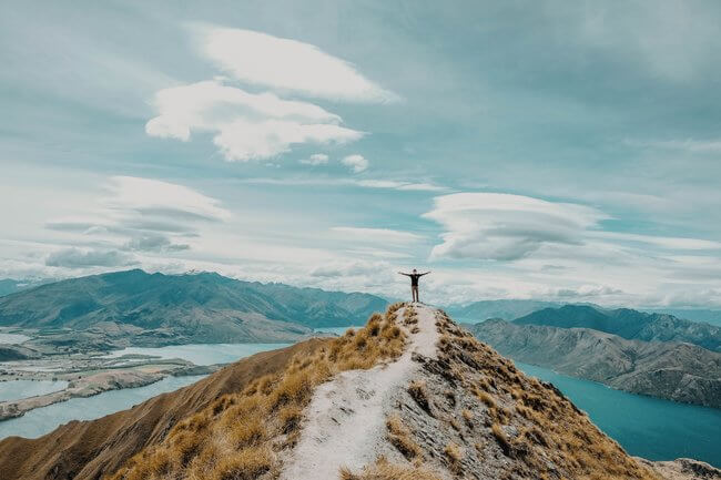 man standing on mountain top over lakes New Zealand