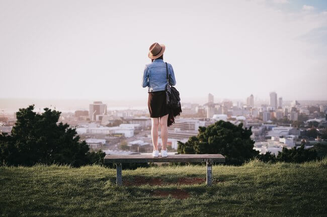 woman standing on bench over looking Auckland New Zealand