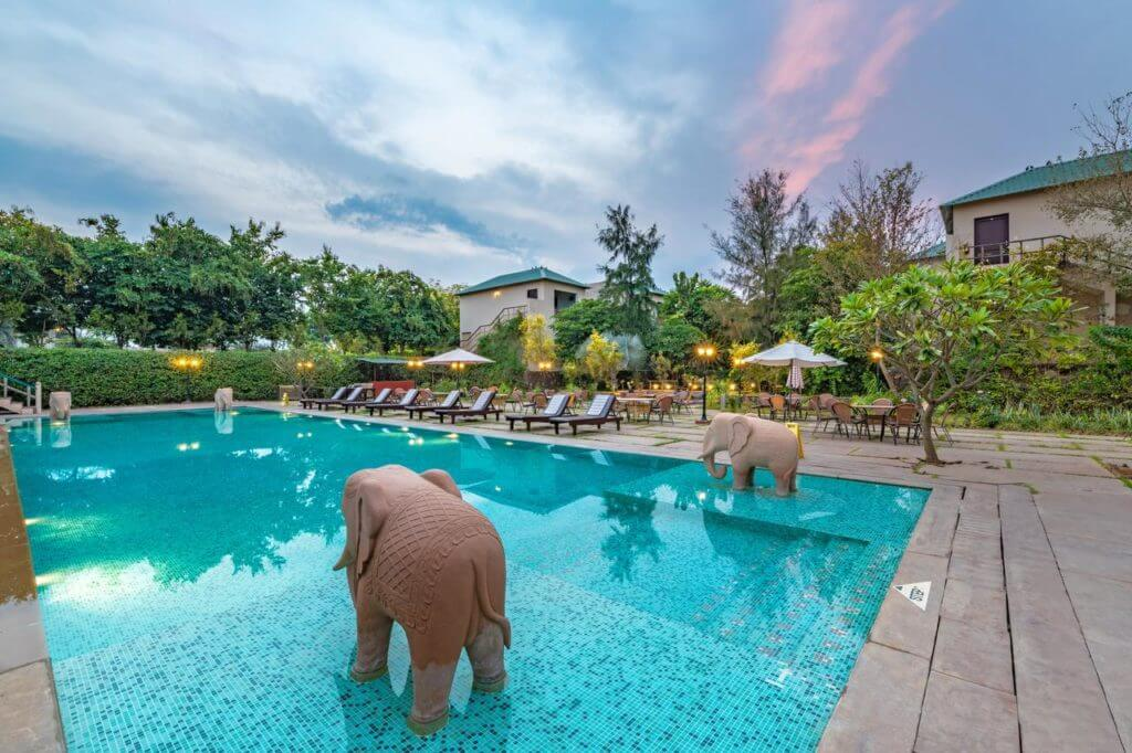 elephant statue in the pool of the Ranthambore Kothi hotel, with bungalows in background