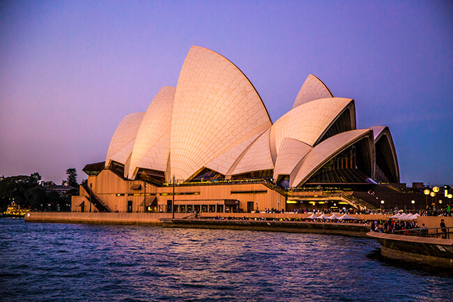 Sydney Opera House up close, amply lit by purple sky and waters below