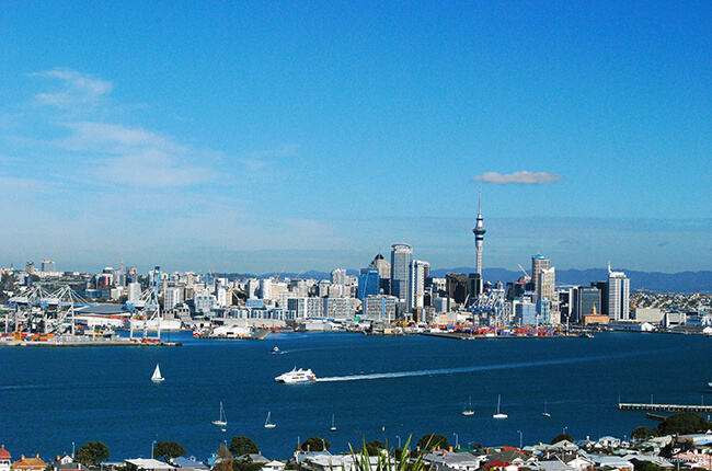Bright photo of Auckland skyline at daytime, with boats sailing in the harbour