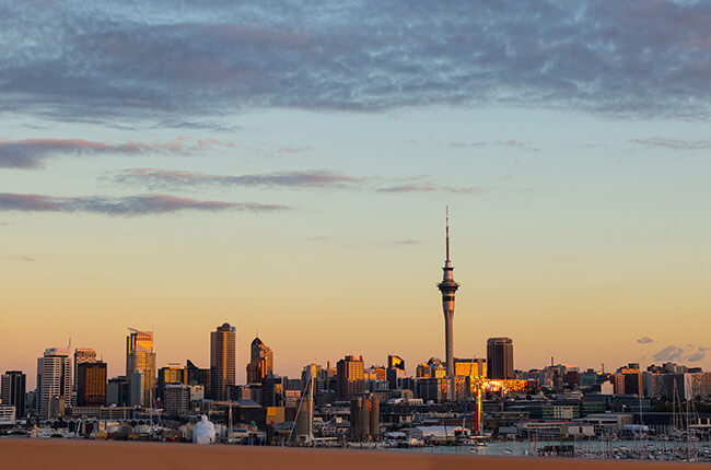 Auckland skyline in the far distance, with the Sky Tower reaching high into the sky at sunrise.
