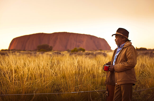 Aboriginal-dressed man stood in front of the culturally historic Ayers rock