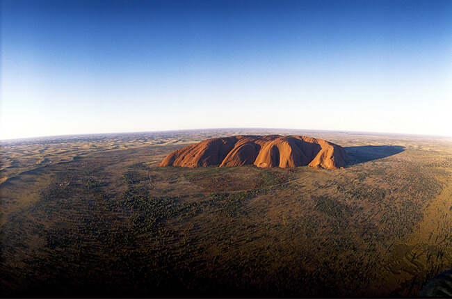 Ayers rock from above, showing the pimple-like structure sat among the flat desert