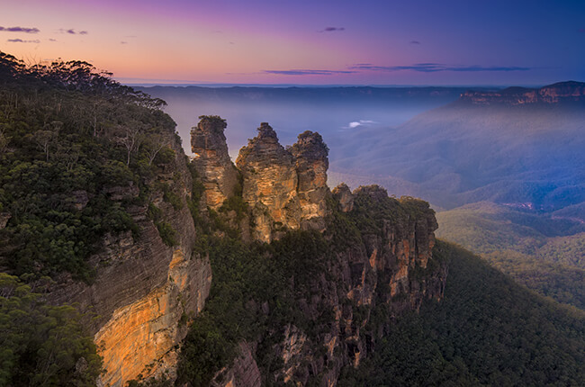 Photo of the three sisters in the Blue Mountains at dawn, with rippling hills covered in vegetation in background