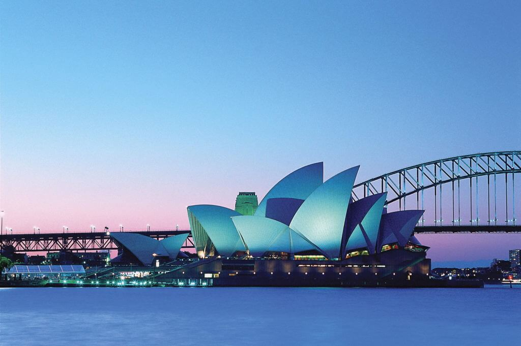 Sydney Opera House at dusk, lit up blue that imitates the pale blue colour of the sky.