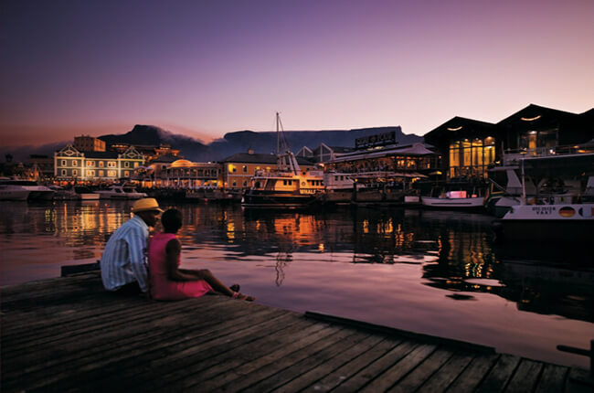 Couple sitting together at the end of a pier in Cape Town Bay, with docked boats and waterfront restaurants in the distance