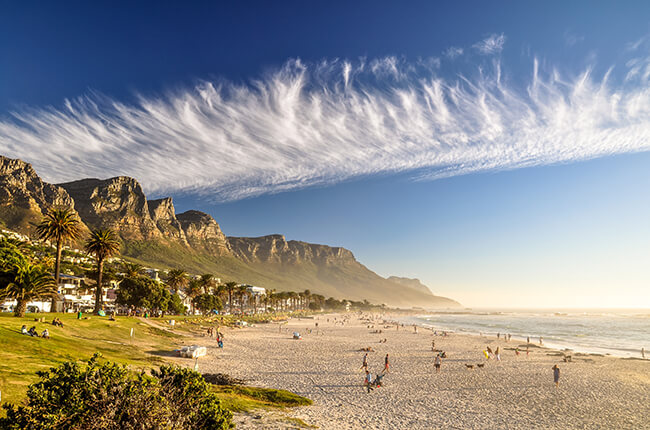 Cape Town beach at daytime, with wispy clouds interrupting the clear blue skies, and the Table mountains in the background