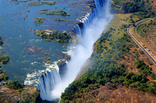 Aerial shot of Victoria Falls, with water disappearing into a gorge, and mist shrouding the pool below