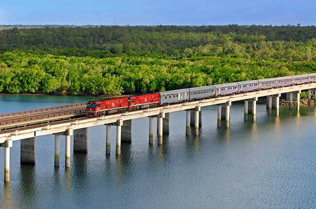 The Ghan train travelling over a bridge separating dense forest