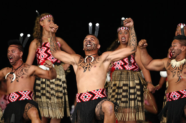 Maori men and women performing the famous war dance; the Haka