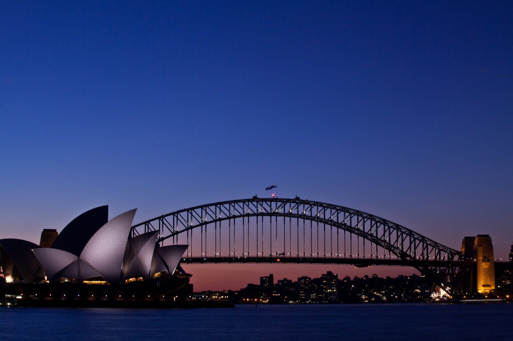 Sydney harbour bridge just after sunset, with Sydney Opera House in foreground lit up