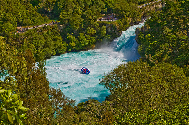The emerald waters of Huka Falls surrounded by the green vegetation of the forest. Shotover Jet in the centre of the plunge pool