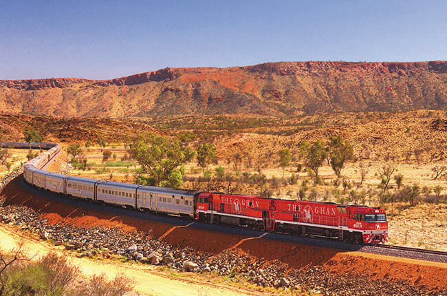 The Ghan train passing through the cobalt red land of the outback
