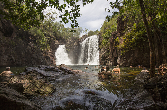 Photo of isolated Katherine Gorge, surrounded by jagged walls and shrubbery. Waterfall in the centre of the image, and swimmers in foreground