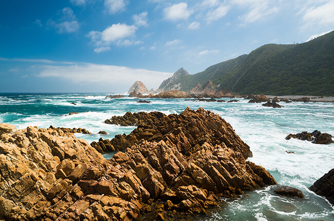 Jagged Rocks of Knysna in the white water, with green hills protecting the coast