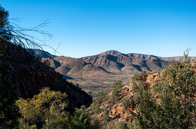 Peering through the valleys of the Western Macdonnell ranges, through to the hills of the valley