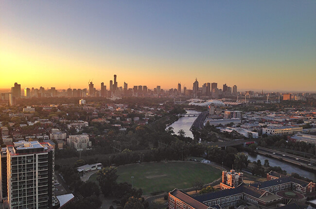 Melbourne at dawn, featuring the CBD in the far distance, and the river and sports grounds in the foreground