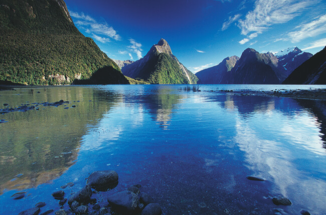 Calm milford sound waters with hills towering overhead