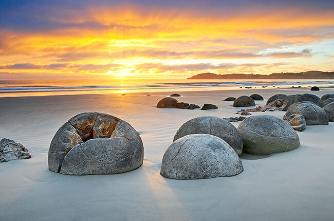 boulders laid upon a white sandy beach with yellow and purple skies
