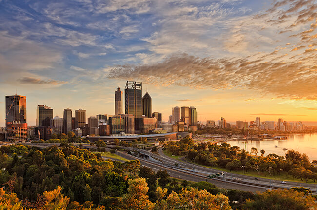Scenic view of Perth, with autumn colours in the dense tree line - sunset reflecting in the skyscrapers