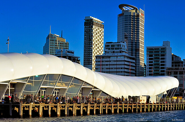 The wave-like architecture of the Queens Wharf in Auckland, with skyscrapers in the background