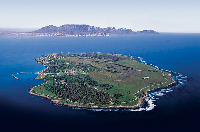 Aerial view of Robben Island, surrounded by deep blue ocean, and Cape Point far away in the background.