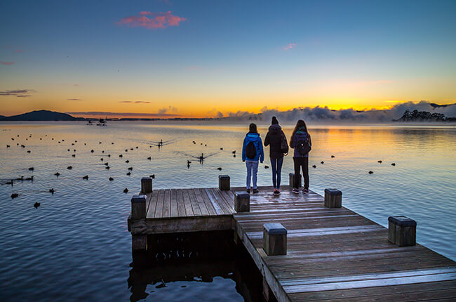 three people stood at the end of a pier in Rotorua, with birds in the calm waters, and the sunset in the background