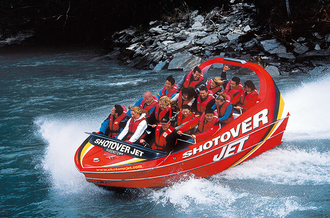 shotover jet full of passengers crashing against the river creating white sprays of waves