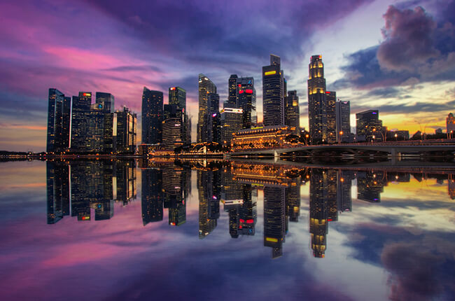 Singapore skyline reflected in the water of the Marina Bay, with streaks of purple in the sky