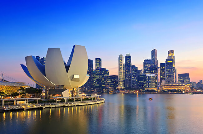 Photo of the famous Art & Science museum at the Marina Bay in Singapore, with skyscrapers behind.
