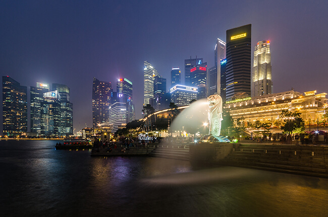 Merlion Statue at twilight with Singapore skyscrapers in background