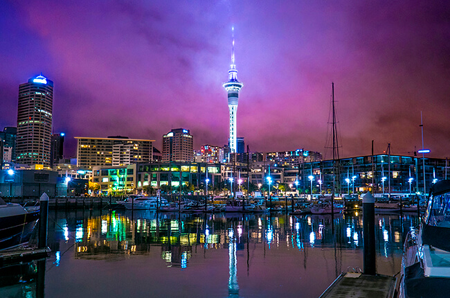 Auckland Harbour lit up at night time, with the Sky Tower dominating the vibrant purple skies