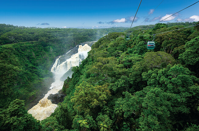 Cairns Skyrail travelling over dense rainforest, with strong waterfall flowing through a gorge