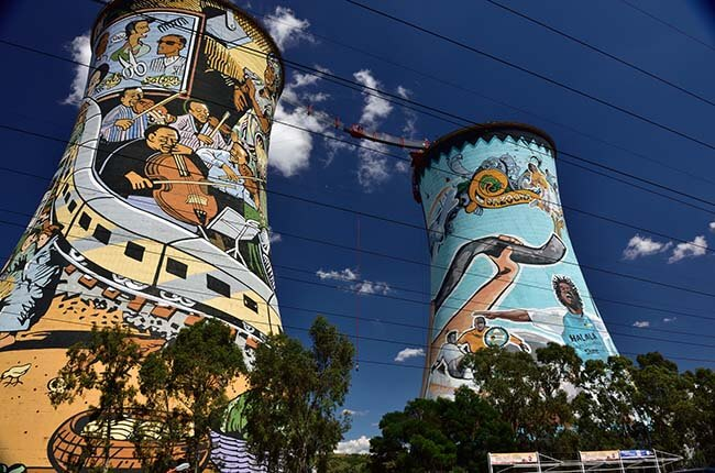 Famous Soweto towers covered in graffiti, with bungee jumper between the two towers