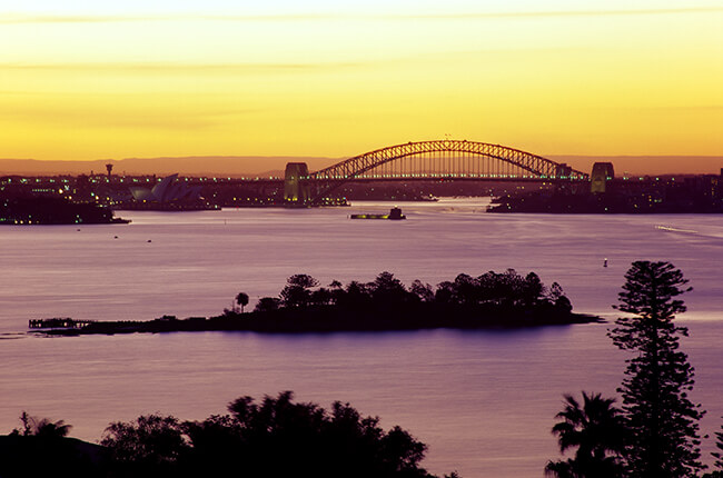 Sydney Harbour at sunset, featuring the Opera House and Harbour Bridge in the distance