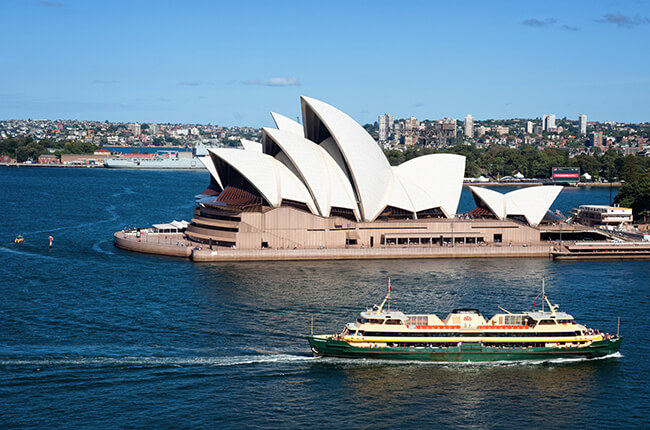 Sydney Opera House with blue water and cruise boat travelling past