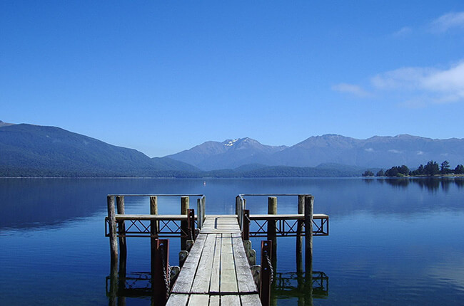 wooden pier of Te Anau, before the stretching lake and hills in the distance