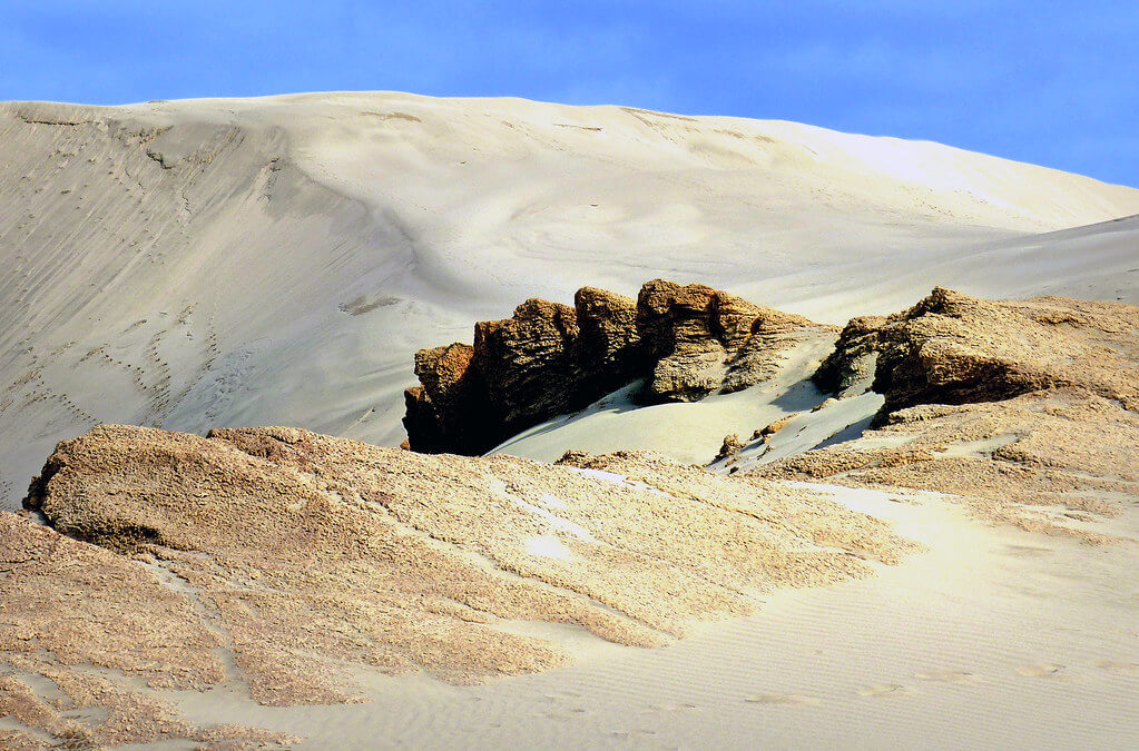 Striking rocks emerging from the pale sand dunes of Te Paki